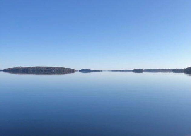 Tyyni järvimaisema ja sininen taivas